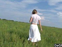 Menina pelada em um campo verde sobre um belo amanhecer